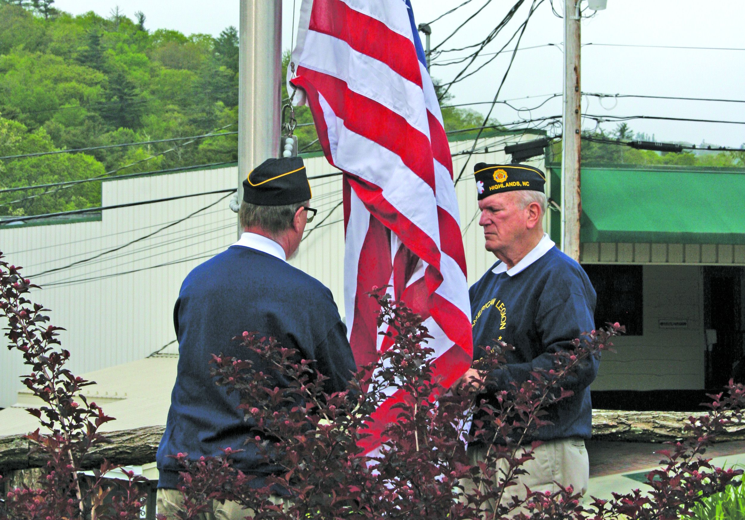 Members of Highlands American Legion Post 370 raise a new flag over the Veteran's Plaza during the annual Memorial Day ceremony on Monday.