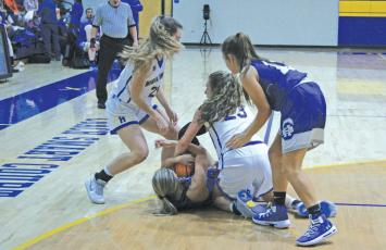 Highlands' players Jordan Carrier (23) and Jeslyn Head (22) get on the floor to tie up a Hiwassee Dam player for a jump ball during their game on Friday night. Highlands won the contest 54-48.