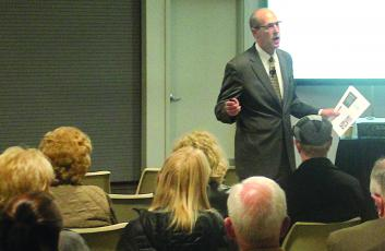 Gibbins Advisors Managing Director Tom Urban speaks to a crowd during a public forum in Highlands.