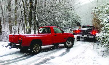 About a dozen vehicles were stranded on NC 106 between Bartram Way and Turtle Pond Road as snow fell on Highlands Friday morning.