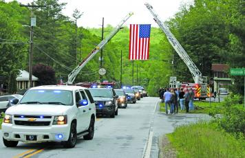 A line of emergency vehicles nearly a mile long escorted Macon County Sheriff's Office corporal David Head's body to Scaly Mountain Volunteer Fire Department where a celebration of life service was held on Thursday.
