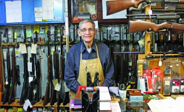 Photo by Will Woolever Buck Ledbetter stands behind the counter of his store, Buck's Gun Shop, in Franklin.