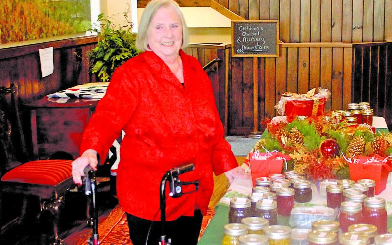 Mary Ann Creswell sets up a table following the Highlands Christmas Parade at the Church of the Incarnation.