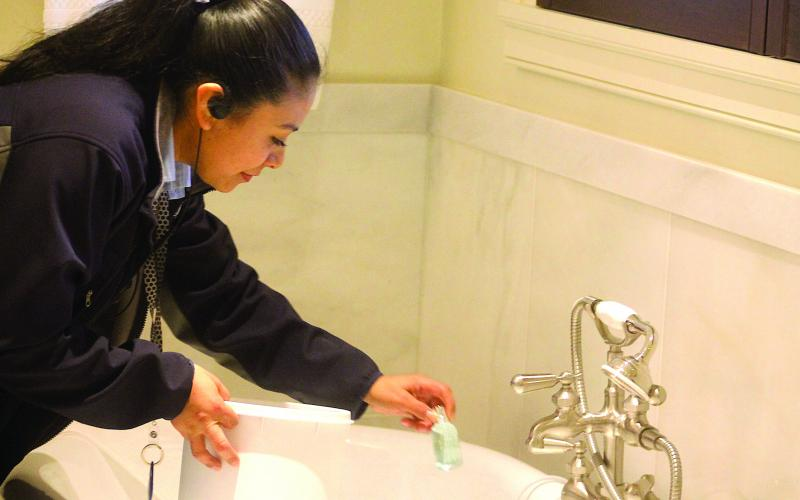 Sandra Valero, housekeeping supervisor with Old Edwards Inn separates single-use plastic shampoo and conditioner bottles for recycling.
