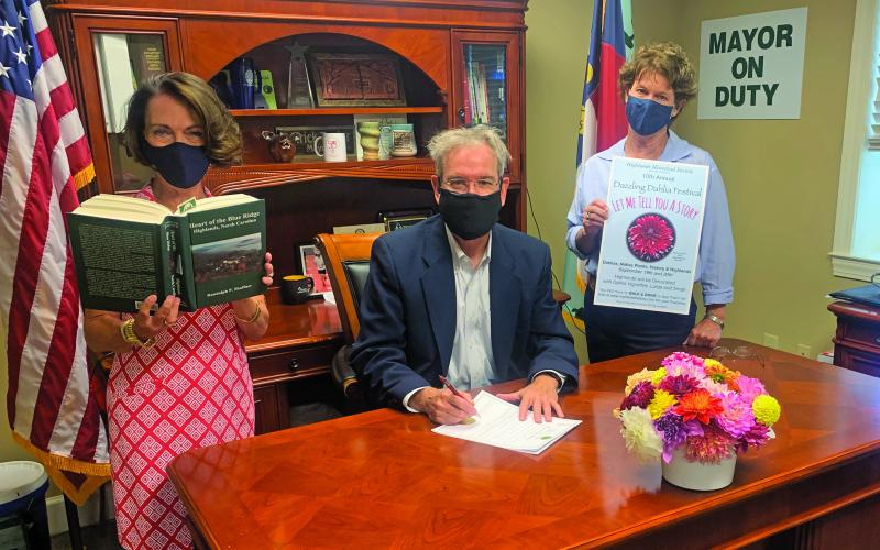 Highlands Mayor Patrick Taylor signs a proclamation celebrating this weekend's 10th annual Dahlia Festival. From left, Kim Daugherty holding the book, Taylor and Lisa Dailey.